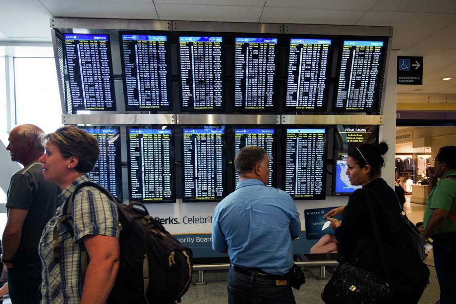 Passengers waiting for the reopening of terminal B crowd around message boards at Terminal C of George Bush Intercontinental Airport on Thursday, May 2, 2013, in Houston. Officials said an armed male suffered at least one gunshot wound near a ticket counter in the pre-screening area of Terminal B of Bush Intercontinental Airport. The incident prompted the closing of terminal B, diverting passengers and delaying flights. ( Smiley N. Pool / Houston Chronicle ) Photo: Smiley N. Pool, Smiley Pool  / © 2013  Houston Chronicle