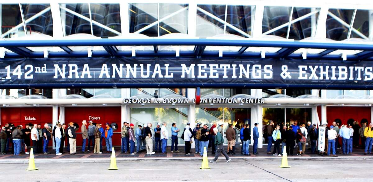 Convention goers line up outside of the George R. Brown Convention Center in Houston, site of the 2013 NRA Convention, Friday, May 3, 2013.