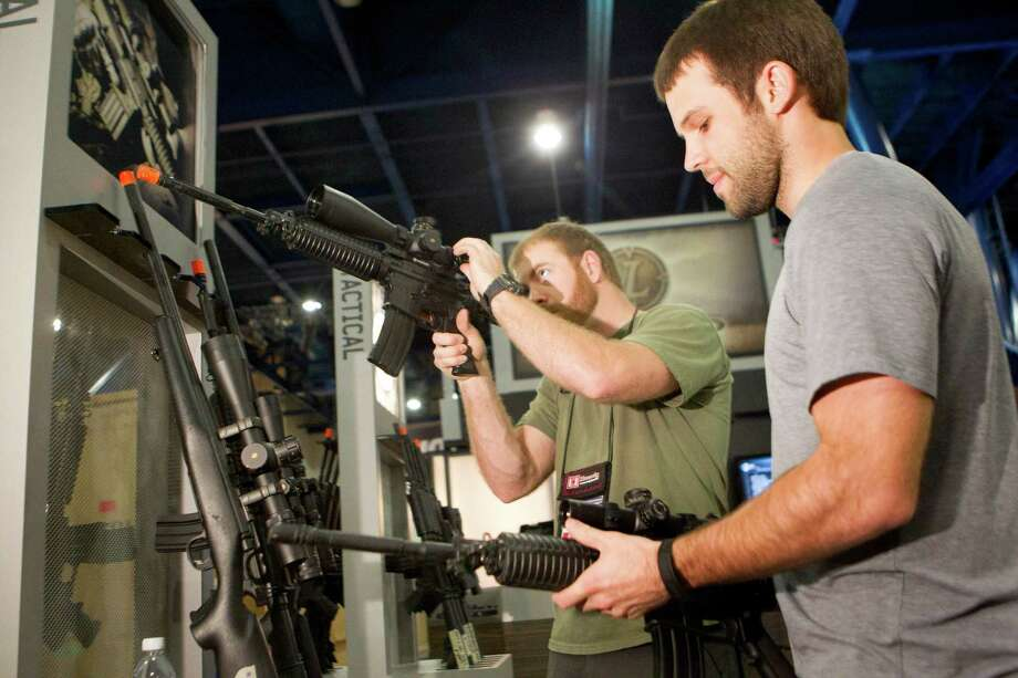 Riley McElroy, right, and Jayden Quinlan, left with Hornady ammunition get a look at firearms in the Leupold Scopes booth as exhibitors began setting up in preparation for the National Rifle Association's 142 Annual Meetings and Exhibits at the George R. Brown Convention Center Thursday, May 2, 2013, in Houston.  The 2013 NRA Annual Meetings and Exhibits runs from Friday, May 3, through Sunday, May 5.  More than 70,000 are expected to attend the event with more than 500 exhibitors represented. The convention will features training and education demos, the Antiques Guns and Gold Showcase, book signings, speakers including Glenn Beck, Ted Nugent and Sarah Palin as well as NRA Youth Day on Sunday Photo: Johnny Hanson, Houston Chronicle / © 2013  Houston Chronicle