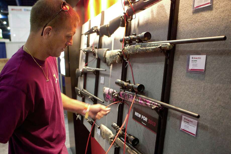 Chet Harris sets up the Savage Arms booth as exhibitors began setting up in preparation for the National Rifle Association's 142 Annual Meetings and Exhibits at the George R. Brown Convention Center Thursday, May 2, 2013, in Houston. 