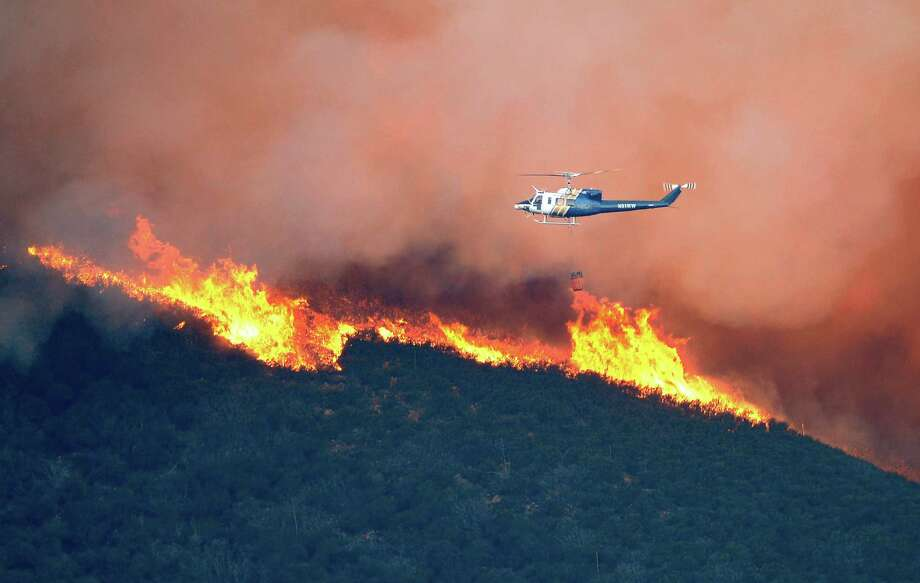 A water dropping helicopter gets ready to make a drop on a fire burring in Point Mugu State Park during a wildfire that burned several thousand acres, Thursday, May 2, 2013, in Ventura County, Calif. Photo: Mark J. Terrill, AP / AP