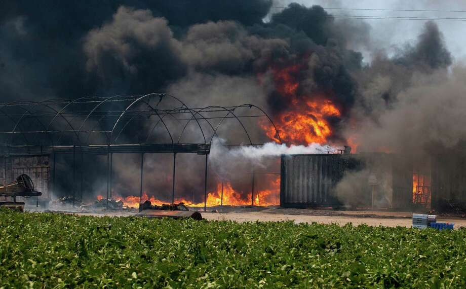 Flames and smoke rise from chemical storage tanks near a strawberry farm in Camarillo, Calif., Thursday, May 2, 2013. Photo: Ringo H.W. Chiu, AP / FR170512 AP