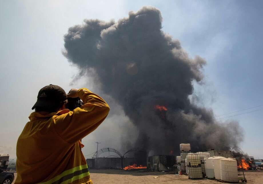 A photographer takes photos as flames and smoke rise from chemical storage tanks near a strawberry farm in Camarillo, Calif., Thursday, May 2, 2013. Photo: Ringo H.W. Chiu, AP / FR170512 AP