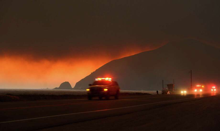 Fire department personnel drive along Pacific Coast Highway near Point Mugu as a thick layer of smoke sits overhead during a wildfire that burned several thousand acres, Thursday, May 2, 2013, in Ventura County, Calif. Photo: Mark J. Terrill, AP / AP