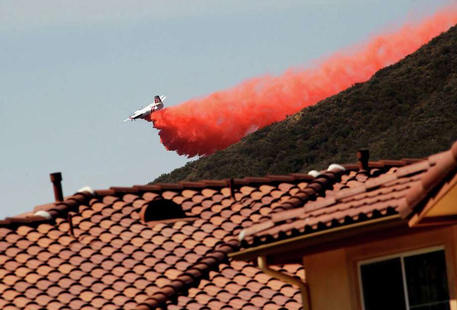 A firefighting aircraft drops fire retardant along a hill side near homes in Thousand Oaks, Calif. on Thursday, May 2, 2013.  A wildfire fanned by gusty Santa Ana winds raged along the fringes of Southern California communities on Thursday, forcing evacuation of homes and a university while setting recreational vehicles ablaze. Photo: Nick Ut, AP / AP