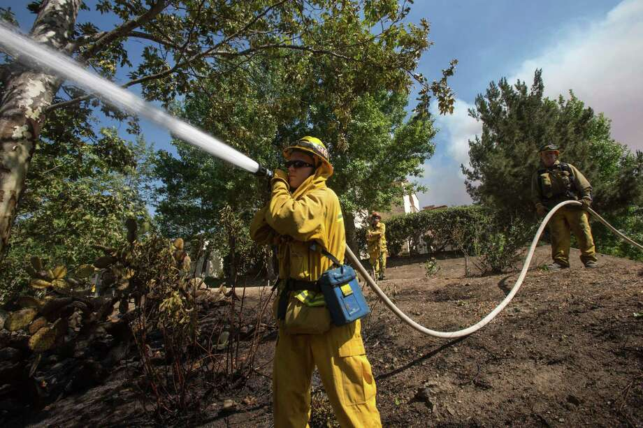 Firefighters douse a burned area along the hillside near the student dorm of California State University, Channel Islands in Camarillo, Calif., Thursday, May 2, 2013. Photo: Ringo H.W. Chiu, AP / FR170512 AP