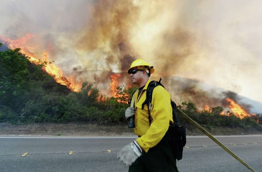 CAMARILLO, CA - MAY 02: A US Forestry fire fighter preapres to take on an out of control wildfire on May 2, 2013 in Camarillo, California. Hundreds of firefighters are battling wind and dry conditions as over 6000 acres have already been burned northwest of Los Angeles. Photo: Kevork Djansezian, Getty Images / 2013 Getty Images