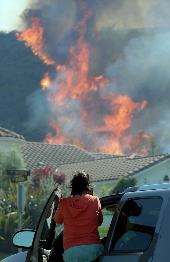 NEWBURY PARK, CA - MAY 02:  Residents look on as a back fire set by firefighters consumes the hillsdie behind their homes during an out of control wildfire on May 2, 2013 in Camarillo, California.  Hundreds of firefighters are battling wind and dry conditions as over 6000 acres have already been burned northwest of Los Angeles. Photo: Kevork Djansezian, Getty Images / 2013 Getty Images