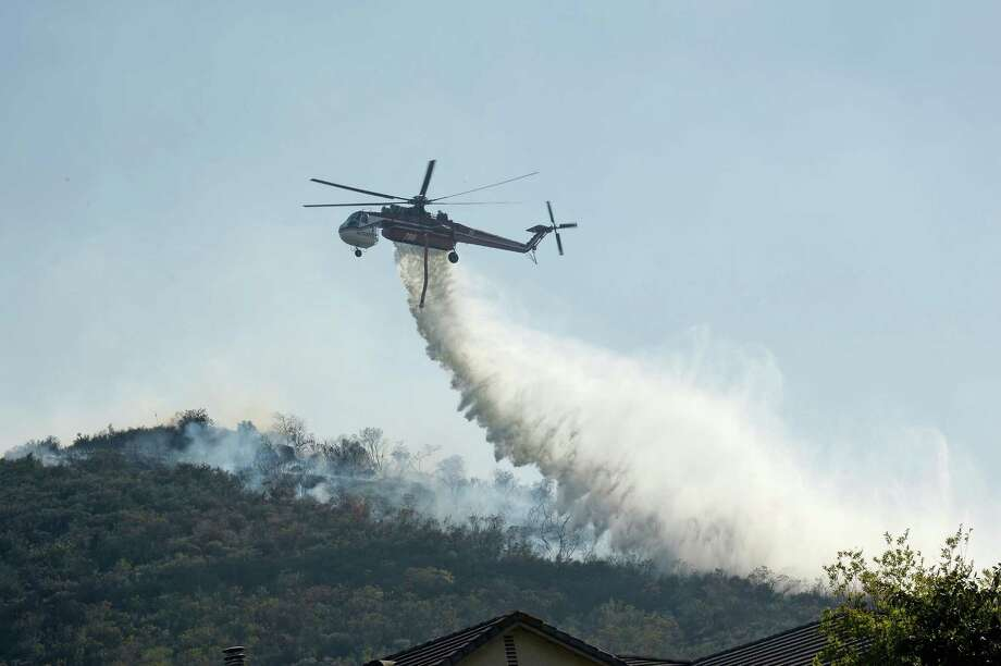 NEWBURY PARK, CA - MAY 02:  Fire fighting helicopters make water drops onto a hillsdie behind homes threatened by the out of control wildfire on May 2, 2013 in Newbury Park, California.  Hundreds of firefighters are battling wind and dry conditions as over 6000 acres have already been burned northwest of Los Angeles. Photo: Kevork Djansezian, Getty Images / 2013 Getty Images