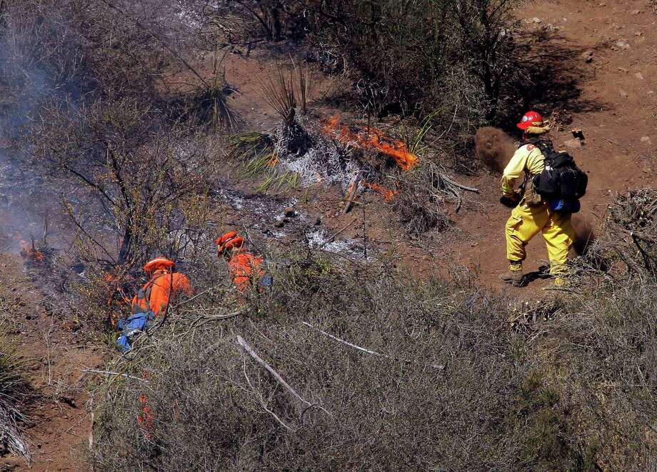 Firefighters clean up a hotspot burning over a hill near Thousand Oaks, Calif., on Thursday, May 2, 2013. The blaze erupted during morning rush hour along U.S. 101 in the Camarillo area about 50 miles west of Los Angeles. It quickly charred more than 10 square miles because of winds that have also pushed other damaging blazes across the region. Photo: Nick Ut, AP / AP