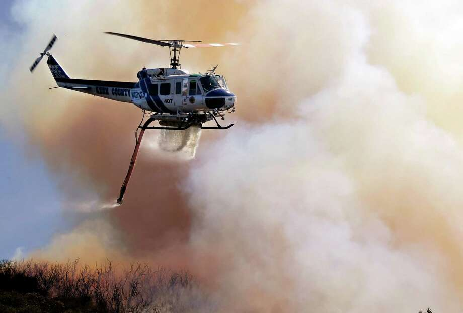 A Kern County Fire helicopter makes a water drop on a hotspot over a hill near Thousand Oaks, Calif. on Thursday, May 2, 2013. Authorities have ordered evacuations of a neighborhood and a university about 50 miles west of Los Angeles where a wildfire is raging close to subdivisions. The blaze on the fringes of Camarillo and Thousand Oaks broke out Thursday morning and was quickly spread by gusty Santa Ana winds. Evacuation orders include California State University, Channel Islands. Photo: Nick Ut, AP / AP
