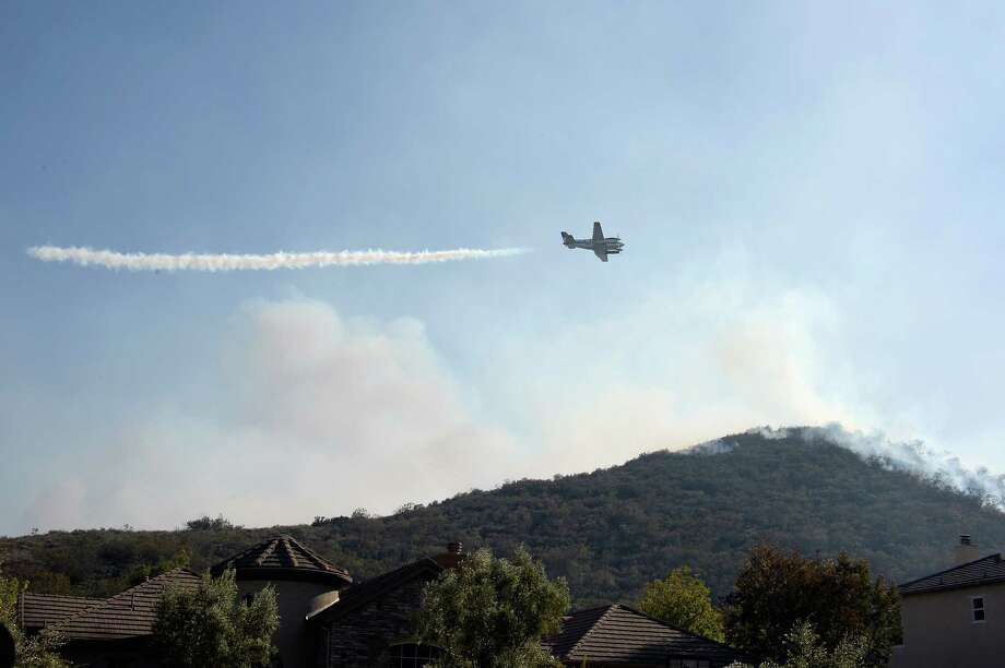 NEWBURY PARK, CA - MAY 02:  A fire fighting spotter plane lays down a trail of smoke to mark the location for water drops on a hillside behind homes threatened by the out of control wildfire on May 2, 2013 in Newbury Park, California.  Hundreds of firefighters are battling wind and dry conditions as over 6000 acres have already been burned northwest of Los Angeles. Photo: Kevork Djansezian, Getty Images / 2013 Getty Images