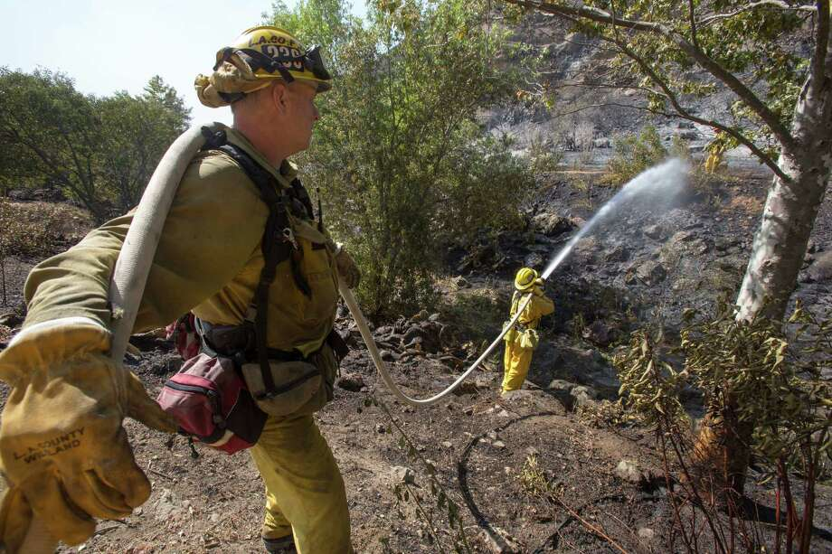 Firefighters douse a burned area along the hillside near the student dorm of  Cal State, Channel Islands in Camarillo, Calif., Thursday, May 2, 2013. Photo: Ringo H.W. Chiu, AP / FR170512 AP