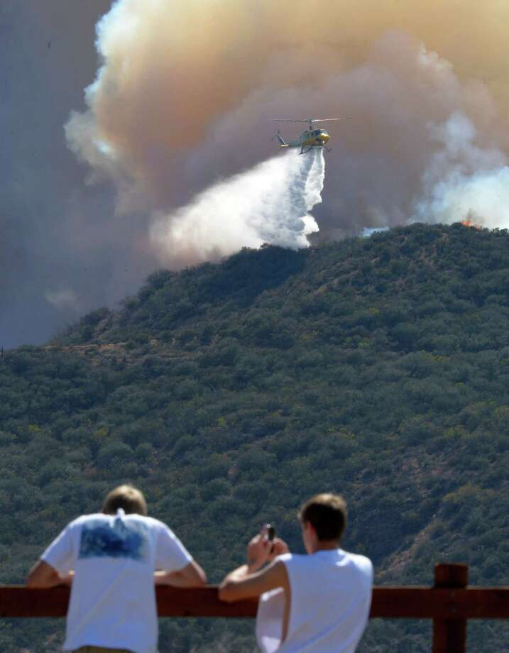 Residents watch a a helicopter drop water during a wildfire that burned several thousand acres, Thursday, May 2, 2013, in Ventura County, Calif. Photo: Mark J. Terrill, AP / AP