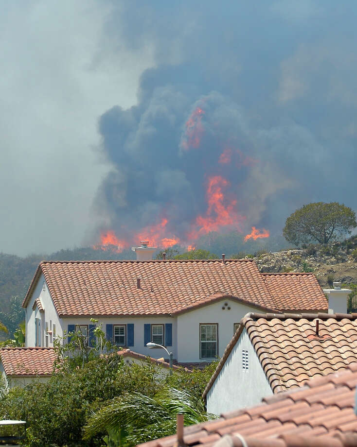 Fire burns behind homes during a wildfire that burned several thousand acres, Thursday, May 2, 2013, in Thousand Oaks, Calif. Photo: Mark J. Terrill, AP / AP