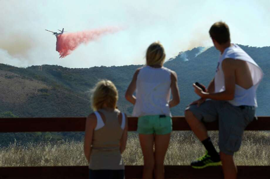 Residents watch an air tanker drop fire retardant during a wildfire that burned several thousand acres, Thursday, May 2, 2013, in Ventura County, Calif. Photo: Mark J. Terrill, AP / AP