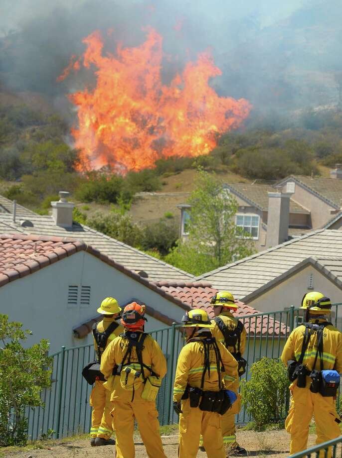 Firefighter looks on as fire burns behind homes during a wildfire that burned several thousand acres, Thursday, May 2, 2013, in Thousand Oaks, Calif. Photo: Mark J. Terrill, AP / AP
