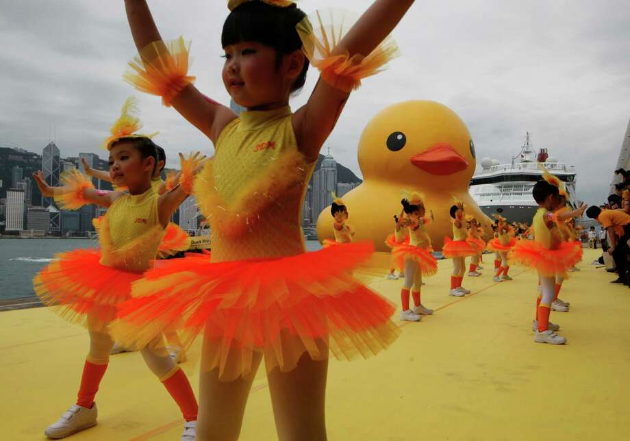 Dancers perform during a welcoming ceremony of a giant Rubber Duck created by Dutch artist Florentijn Hofman in Hong Kong Thursday, May 2, 2013. Since 2007 the 16.5-meter (54-feet)-tall Rubber Duck has traveled to various cites including Osaka, Sydney, Sao Paulo and Amsterdam. Photo: Kin Cheung, AP / AP