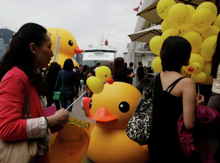 Visitors attend a welcoming ceremony of a giant Rubber Duck created by Dutch artist Florentijn Hofman in Hong Kong Thursday, May 2, 2013. Since 2007 the 16.5-meter (54-feet)-tall Rubber Duck has traveled to various cites including Osaka, Sydney, Sao Paulo and Amsterdam. Photo: Kin Cheung, AP / AP