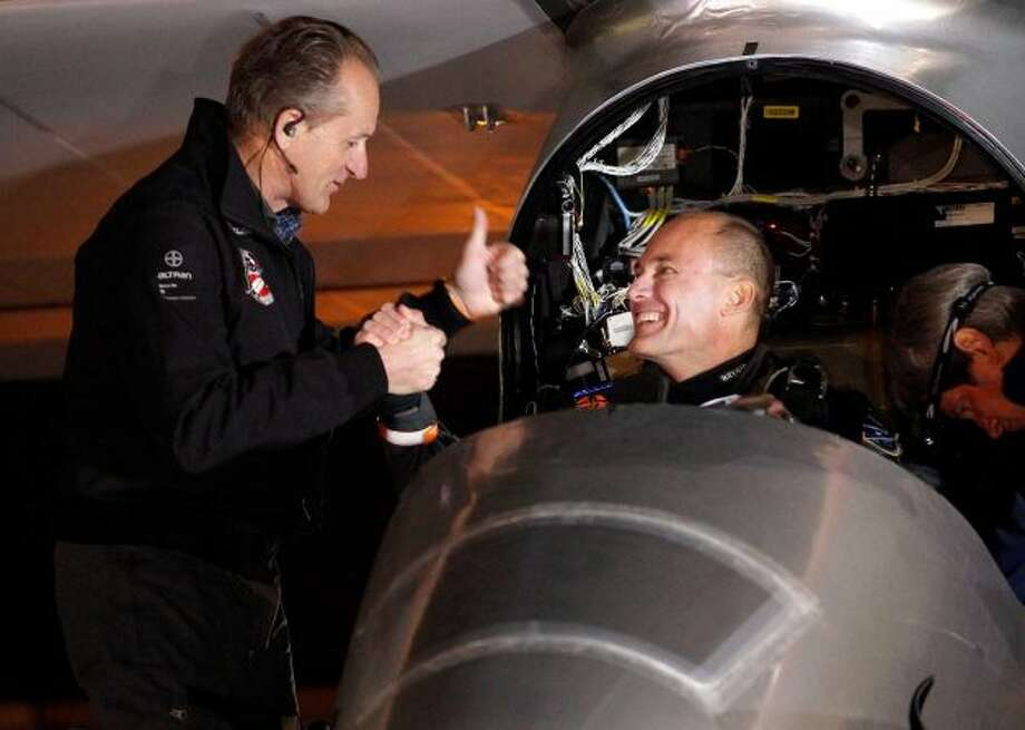 Pilots Bertrand Piccard, right, and André Borschberg, left shake hands before the Solar Impulse plane takes off to embark on a multi-city trip across the United States from Moffett Field NASA Ames Research Center in Mountain View, Calif., Friday, May 3, 2013. Solar Impulse, considered the world's most advanced solar-powered plane, will stop for seven to 10 days at major airports in each city, so the pilots can display and discuss the aircraft with reporters, students, engineers and aviation fans. It plans to reach New York's Kennedy Airport in early July — without using a drop of fuel, its creators said. Photo: Tony Avelar
