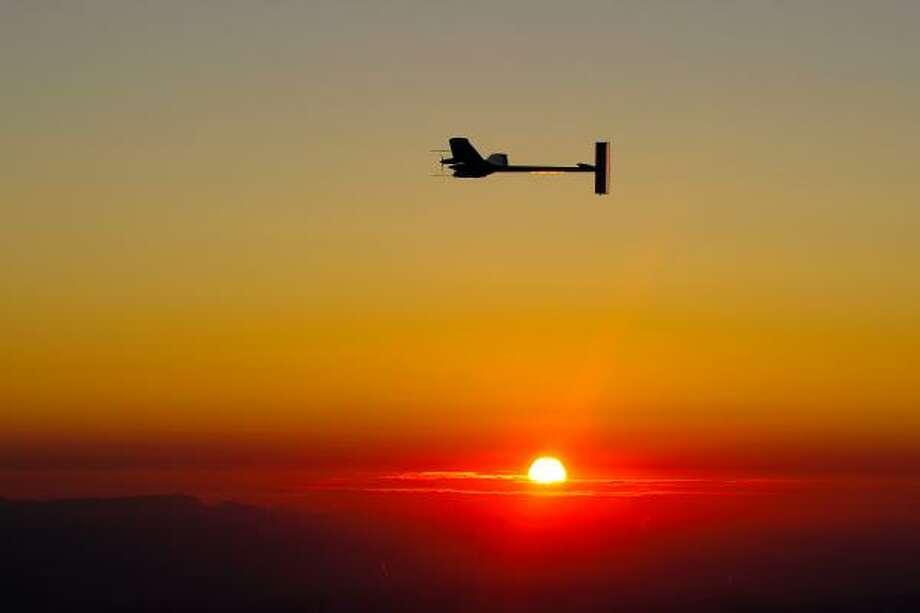The solar impulse begins evening flight as the sun sets over Switzerland in 2010. Photo: Fabrice Coffrini, Solar Impulse