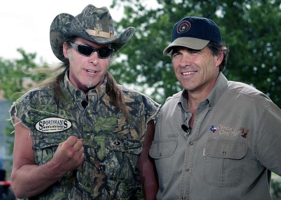 In this file photo, rock musician Ted Nugent, left, and Texas Gov. Rick Perry, right, speak during an appearance on national television in Crawford, Texas, Saturday, June 4, 2005. Hours after Gov. Rick Perry kicked off his second full term in office on Wednesday, Jan. 17, 2007, rocker Ted Nugent helped him celebrate at a black-tie gala, but not all attendees were pleased by the performance. Using machine guns as props, Nugent appeared onstage as the final act of the inaugural ball wearing a cut-off T-shirt emblazoned with the Confederate flag and shouting offensive remarks about non-English speakers, according to people who were in attendance.