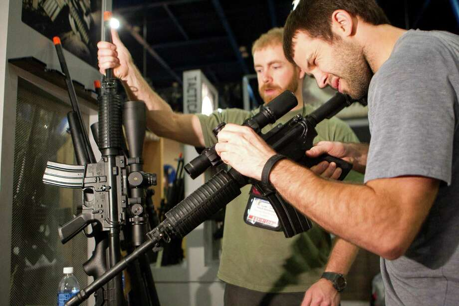 Riley McElroy, right, and Jayden Quinlan, left with Hornady ammunition get a look at firearms in the Leupold Scopes booth as exhibitors began setting up in preparation for the National Rifle Association's 142 Annual Meetings and Exhibits at the George R. Brown Convention Center Thursday, May 2, 2013, in Houston. 