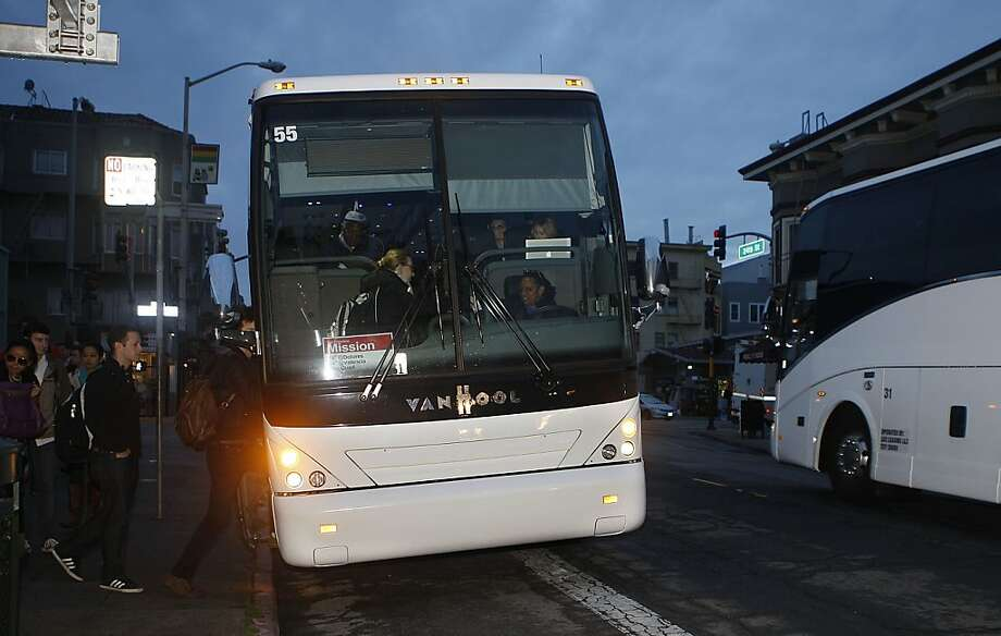 A shuttle to the Google campus (left) loading passengers on the 24th at Valencia street bus stop in San Francisco, Calif., as the Facebook shuttle passes by on right on Tuesday, October 23, 2012.  San Francisco supervisor John Avalos has introduced legislation to regulate these private shuttles. Photo: Liz Hafalia, The Chronicle