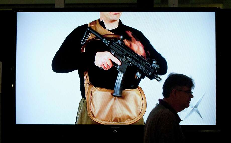 Mike Canavan with Canavan Scenic and Light Inc., works on setting up the audio and visual equipment in the Sig Sauer booth as exhibitors began setting up in preparation for the National Rifle Association's 142 Annual Meetings and Exhibits at the George R. Brown Convention Center Thursday, May 2, 2013, in Houston.  The 2013 NRA Annual Meetings and Exhibits runs from Friday, May 3, through Sunday, May 5.  More than 70,000 are expected to attend the event with more than 500 exhibitors represented. The convention will features training and education demos, the Antiques Guns and Gold Showcase, book signings, speakers including Glenn Beck, Ted Nugent and Sarah Palin as well as NRA Youth Day on Sunday Photo: Johnny Hanson, Houston Chronicle / © 2013  Houston Chronicle