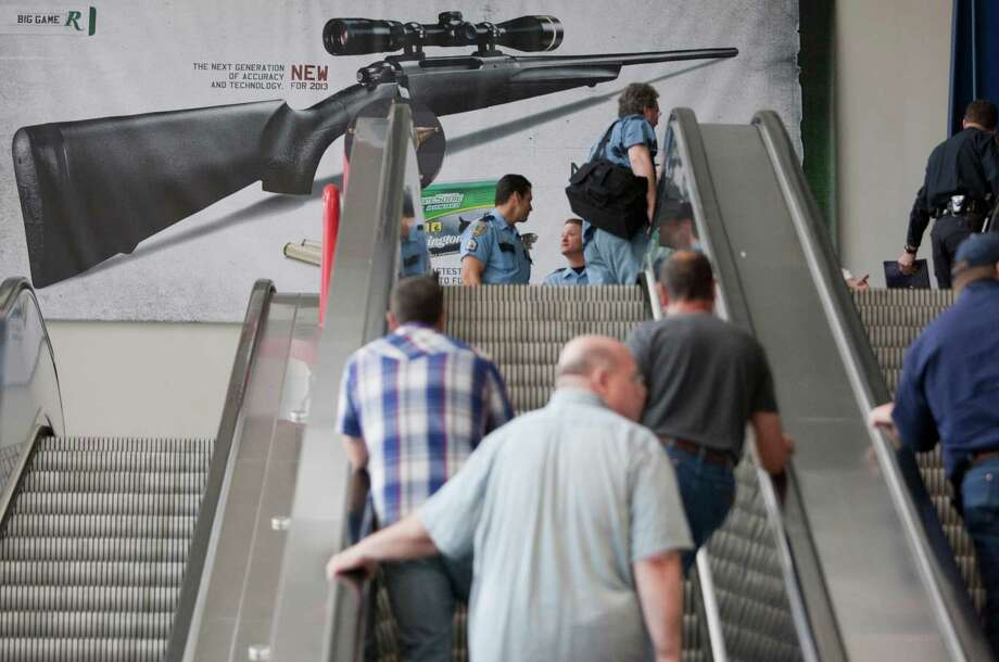 NRA attendees make their way into the George R. Brown Convention Center before the opening of the National Rifle Association's 142 Annual Meetings and Exhibits at the George R. Brown Convention Center Thursday, May 2, 2013, in Houston.  The 2013 NRA Annual Meetings and Exhibits runs from Friday, May 3, through Sunday, May 5.  More than 70,000 are expected to attend the event with more than 500 exhibitors represented. The convention will features training and education demos, the Antiques Guns and Gold Showcase, book signings, speakers including Glenn Beck, Ted Nugent and Sarah Palin as well as NRA Youth Day on Sunday Photo: Johnny Hanson, Houston Chronicle / © 2013  Houston Chronicle