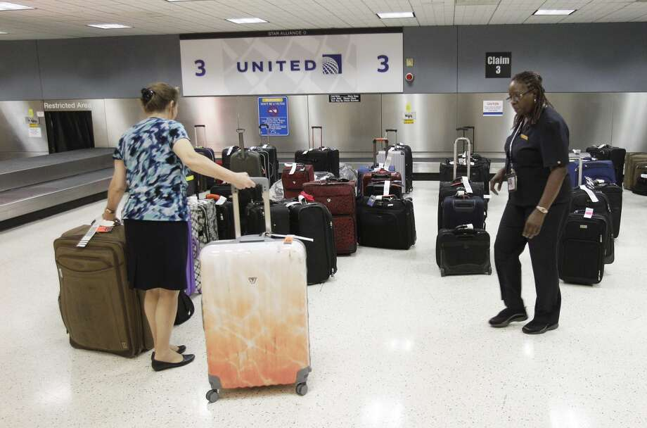 United employees collect bags on the baggage level terminal B after a shooting in terminal B at IHA Thursday, May 2, 2013. Photo: Melissa Phillip