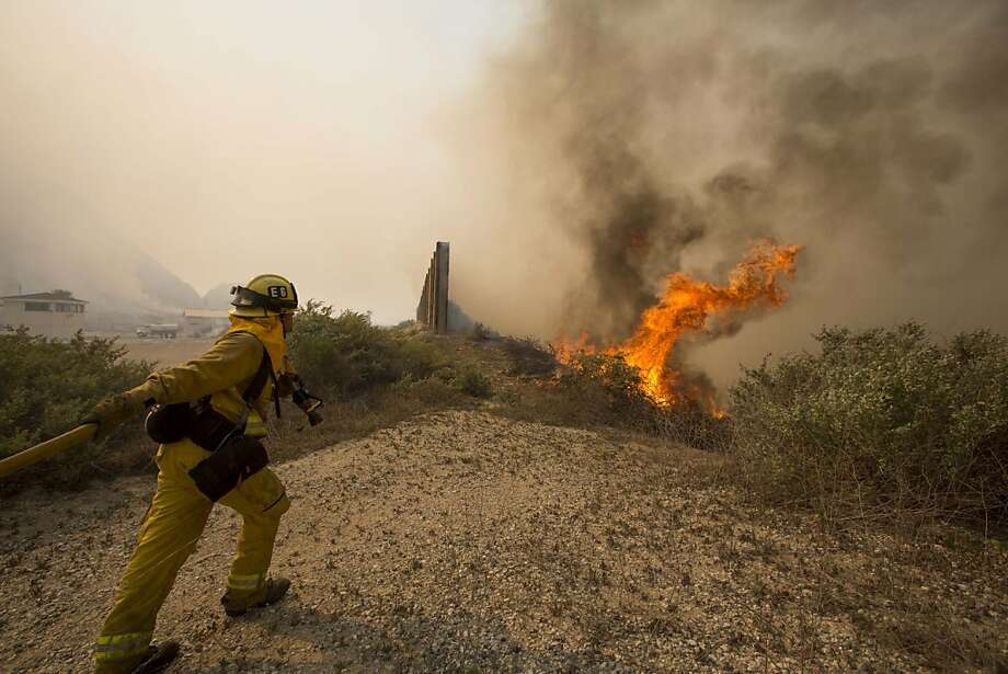 A firefighter rushes to extinguish the wildfire in the Naval Base at Point Mugu, Calif., Friday, May 3, 2013. The 15 1/2-square-mile blaze was only 10 percent contained on Friday, and the work of more than 900 firefighters, aided by air tankers, was just beginning. Photo: Ringo H.W. Chiu, Associated Press