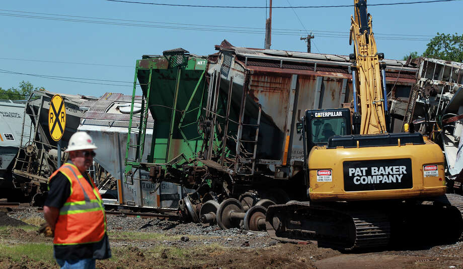 Crews work to clean up a Union Pacific freight train crash that took place in downtown Lytle, Texas south of San Antonio Friday May 3, 2013. Lytle Police Lt. Matt Dear said the northbound train mostly had empty cars and there were no injuries. The cause of the accident is being investigated. Photo: JOHN DAVENPORT, SAN ANTONIO EXPRESS-NEWS / ©San Antonio Express-News/Photo may be sold to the public