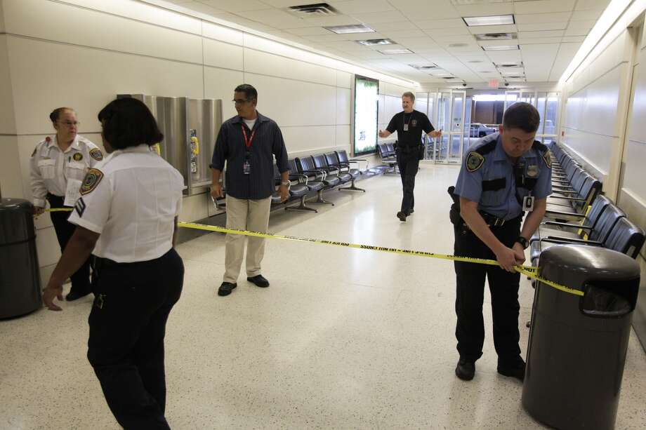 Police tape off exit in baggage level after  a shooting in terminal B at Bush Intercontinental Airport, Thursday, May 2, 2013. Photo: Melissa Phillip