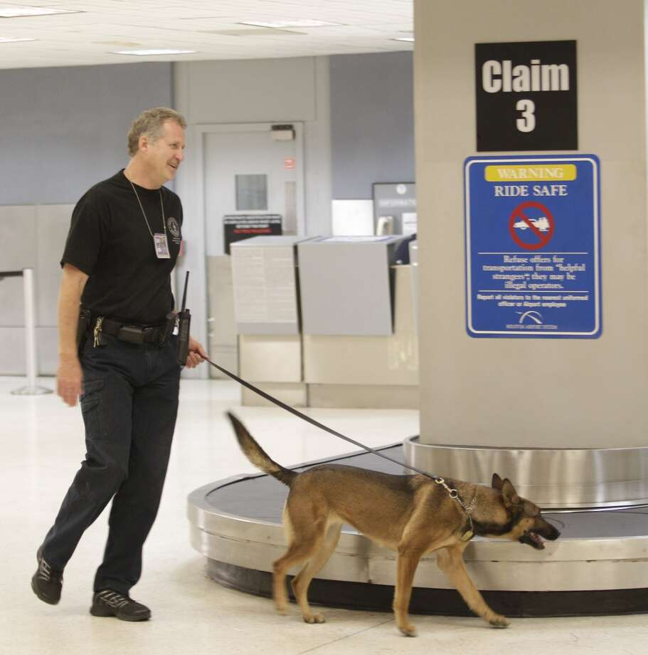 An HPD K9 police officer sweeps the baggage level after a shooting in Terminal B at Bush Intercontinental Airport, Thursday, May 2, 2013.  Photo: Melissa Phillip