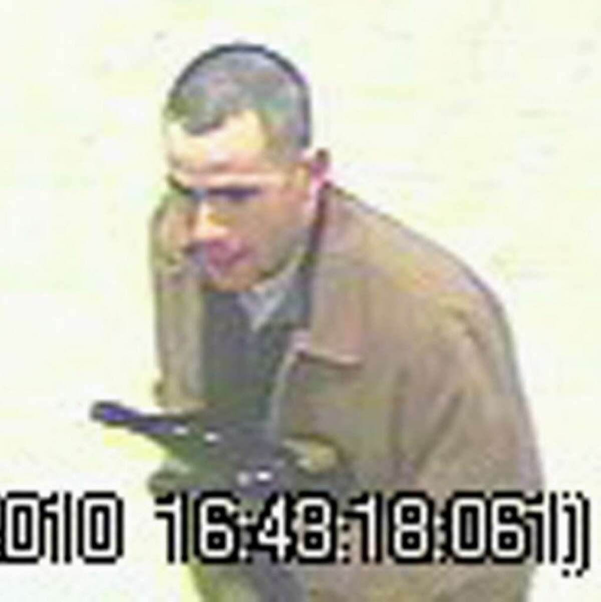 Surveillance camera images of man suspected of spending spree with stolen credit cards. The suspect is described as a white man, about 6 feet tall with a medium build and very short or thinning dark hair. He was dressed in khaki pants and a tan jacket, and wore glasses when he was in one of the stores. He was driving a newer model four-door Jeep Liberty, gold or tan in color, with a retractable roof.