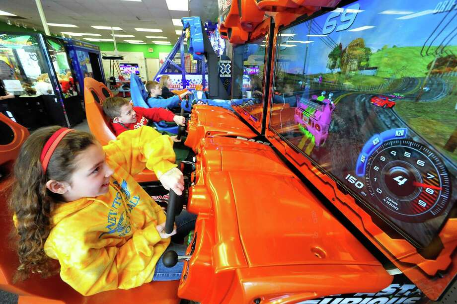 Hannah Cicciari, 10, left, Tyler Clure, 11, center, and Andrew Cicciari, 10, play Fast & Furious Super Cars at the Sandy Hook Arcade Center in Newtown, Conn. Saturday, April 6, 2013. Photo: Michael Duffy / The News-Times