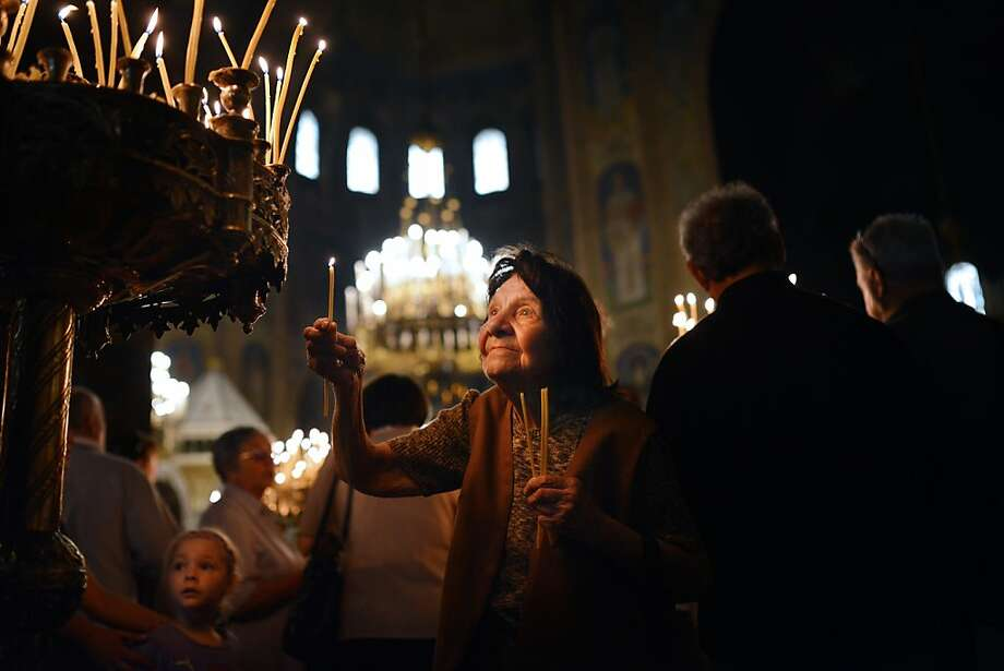 Orthodox Easter: A Bulgarian woman lights a candle during a Good Friday service in the golden-domed Alexander Nevski cathedral in 