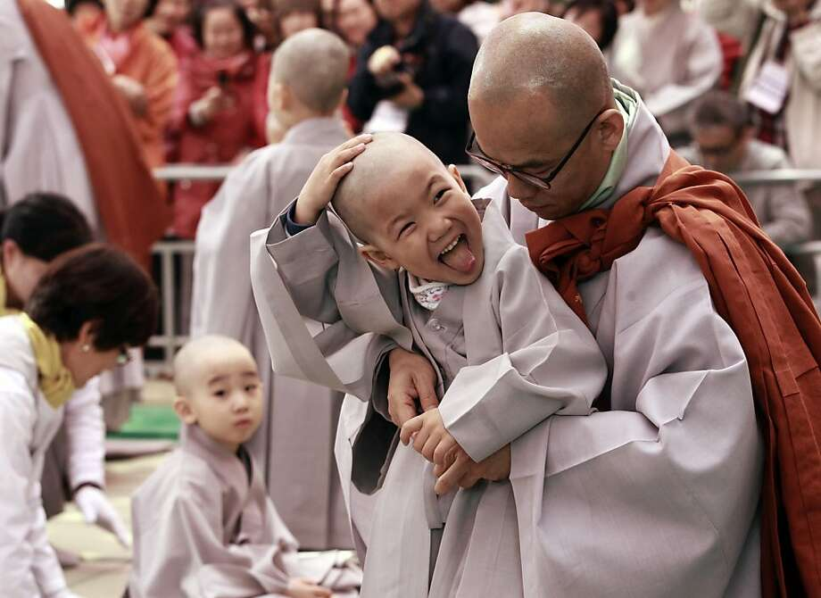 Clean as a whistle:A boy feels his head after getting shaved during a ceremony at the Jogye temple in Seoul. Ten 