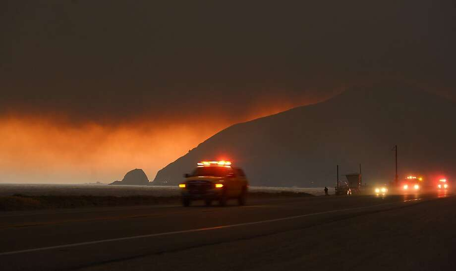 Darkened skies: Fire department personnel drive along the Pacific Coast Highway near Point Mugu as a thick layer of smoke hangs 