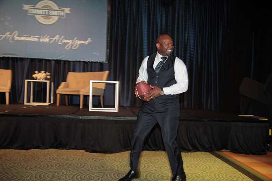 Emmitt Smith tosses a football to Ron DePinho. Photo: Pete Baatz