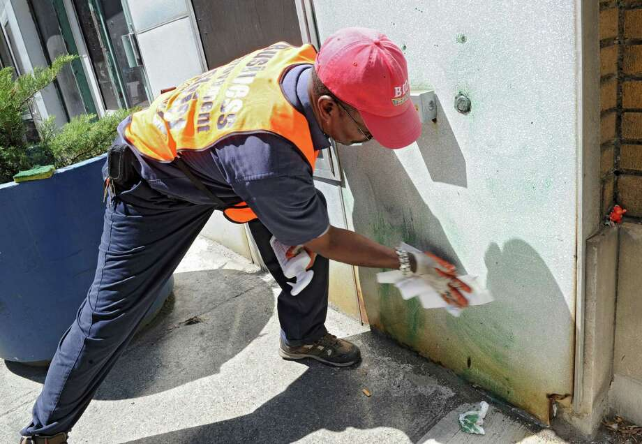 Charles Potts of the Troy Business Improvement District uses Krud Kutter to clean graffiti from a building near the corner of River and Third streets on Friday, May 3, 2013, in Troy, N.Y. Several locations in Troy were vandalized overnight near the Uncle Sam statues installed in and around downtown. (Lori Van Buren / Times Union) Photo: Lori Van Buren / 10022281A