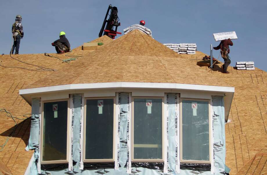Workers stack roofing materials to complete a home in Sugar Land. In the Houston area, construction has begun on 26,000 homes over the past 12 months. Photo: Mayra Beltran, Staff / © 2012 Houston Chronicle