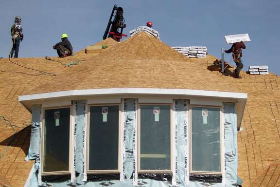 Workers stack roofing materials to complete a home in Sugar Land. In the Houston area, construction has begun on 26,000 homes over the past 12 months.