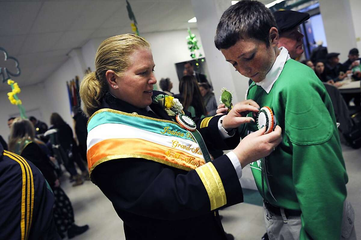 SF Fire Chief Joanne Hayes-White talks pins a button on her son Sean's shirt before the start of the annual St. Patrick's Day Parade in San Francisco, Saturday March 16th, 2013.