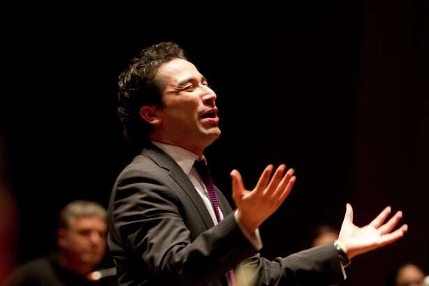 Andrés Orozco-Estrada, a native of Colombia, walks onto the stage to the applause of players at the Houston Symphony at Jones Hall during rehearsal, as he was announced as the new music director to the orchestra, Wednesday, Jan. 16, 2013. ( Karen Warren / Houston Chronicle )