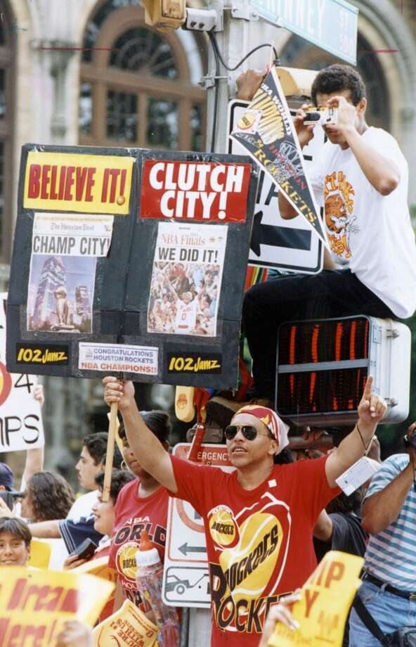 Fans climb on anything stationary to get a good view of the parade. Photo: Chronicle File Photo