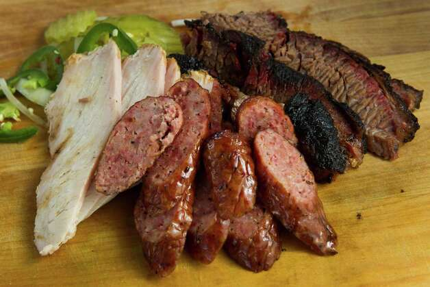 The three-meat plate is shown at Corkscrew BBQ Friday, Feb. 8, 2013, in Spring. ( Brett Coomer / Houston Chronicle ) Photo: Brett Coomer, Houston Chronicle / © 2013 Houston Chronicle