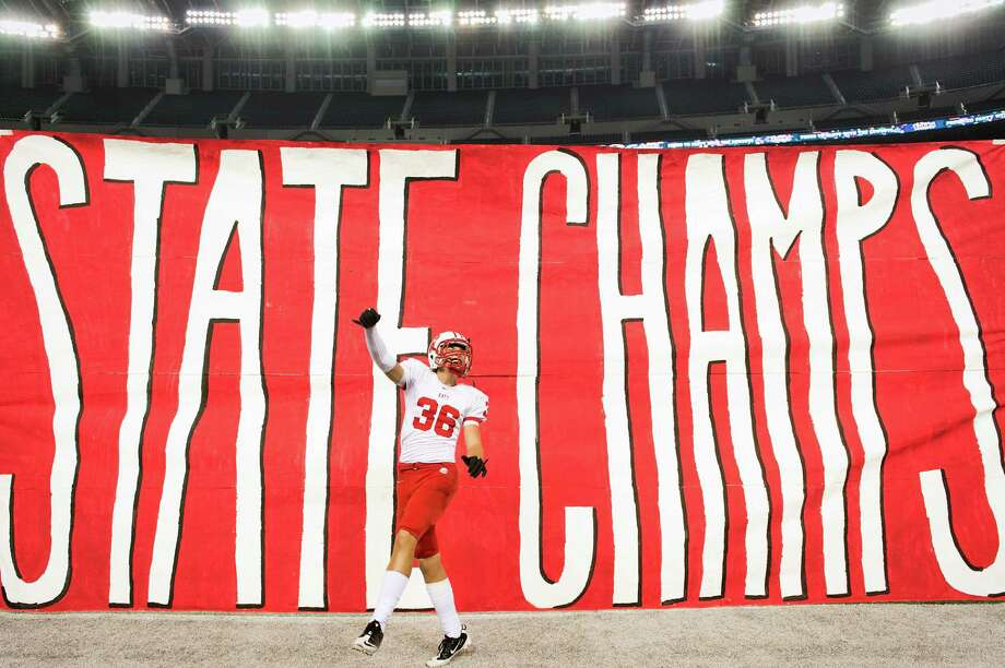 In much of the state's eyes, Katy is symbolized by high school football prowess.. Katy High won state titles in 1997, 2000, 2003, 2007, 2008 and 2012.  Katy wide receiver Peyton Stevenson celebrates in front of a state champs banner after a victory over Cedar Hill in the Class 5A Division II state championship football game at Cowboys Stadium in 2012. n Saturday, Dec. 22, 2012, in Arlington. Photo: Smiley N. Pool, Staff / © 2012  Houston Chronicle