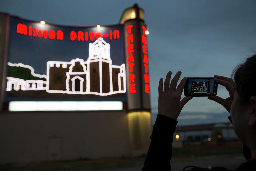 Dina Zavala takes a photo of her handiwork during the official lighting of the recently completed Mission Drive-In Mural at the Mission Drive-In Theatre on Feb. 12, 2013. Zavala, an employee of SRO Associates, worked on the design, painting, neon and marquee of the mural.